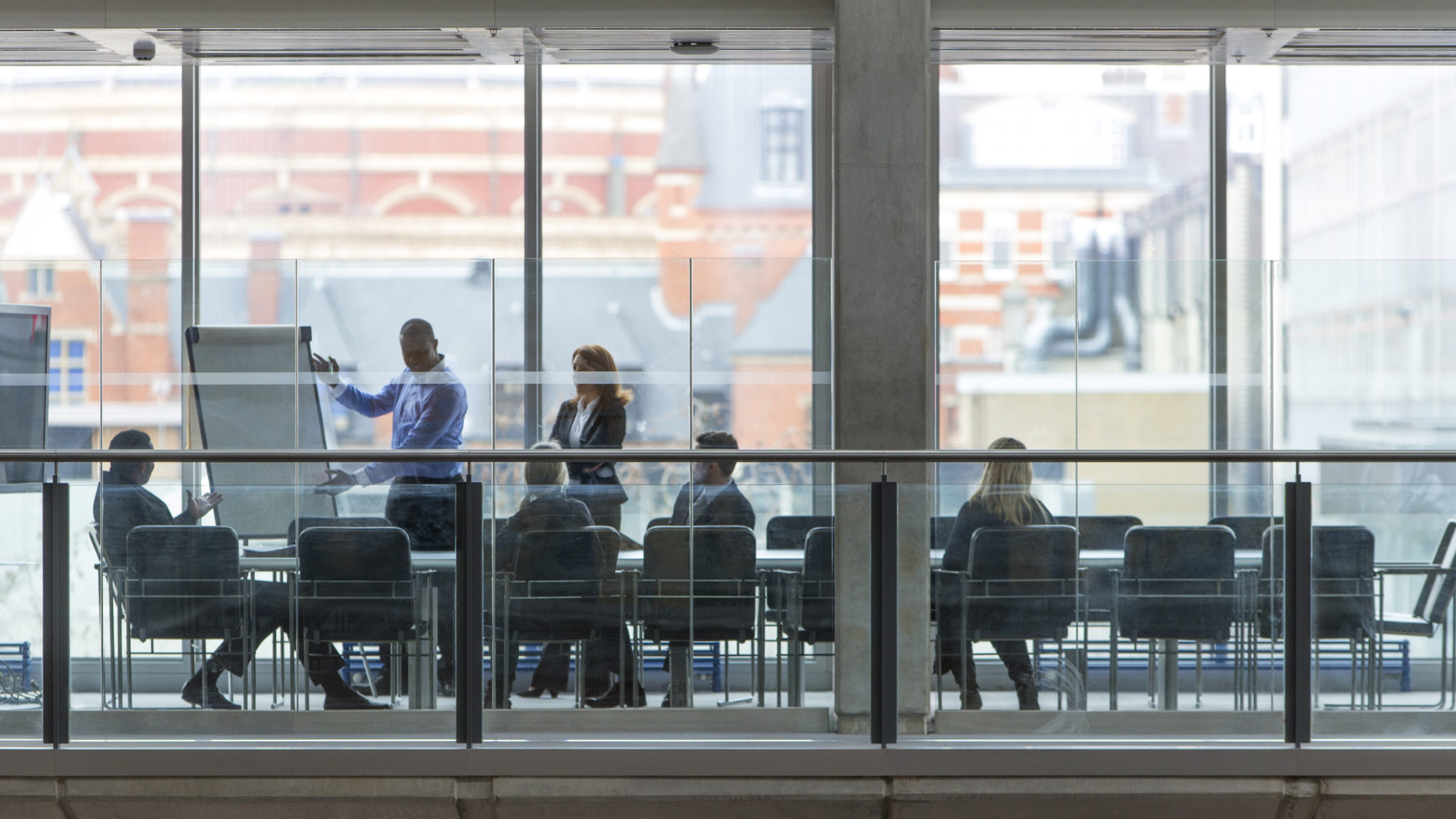 Photo of a group of six business people in a boardroom meeting. Shot at a distance from outside through the glass.